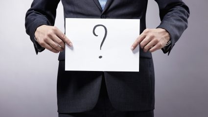 Executive holding sign with questions mark